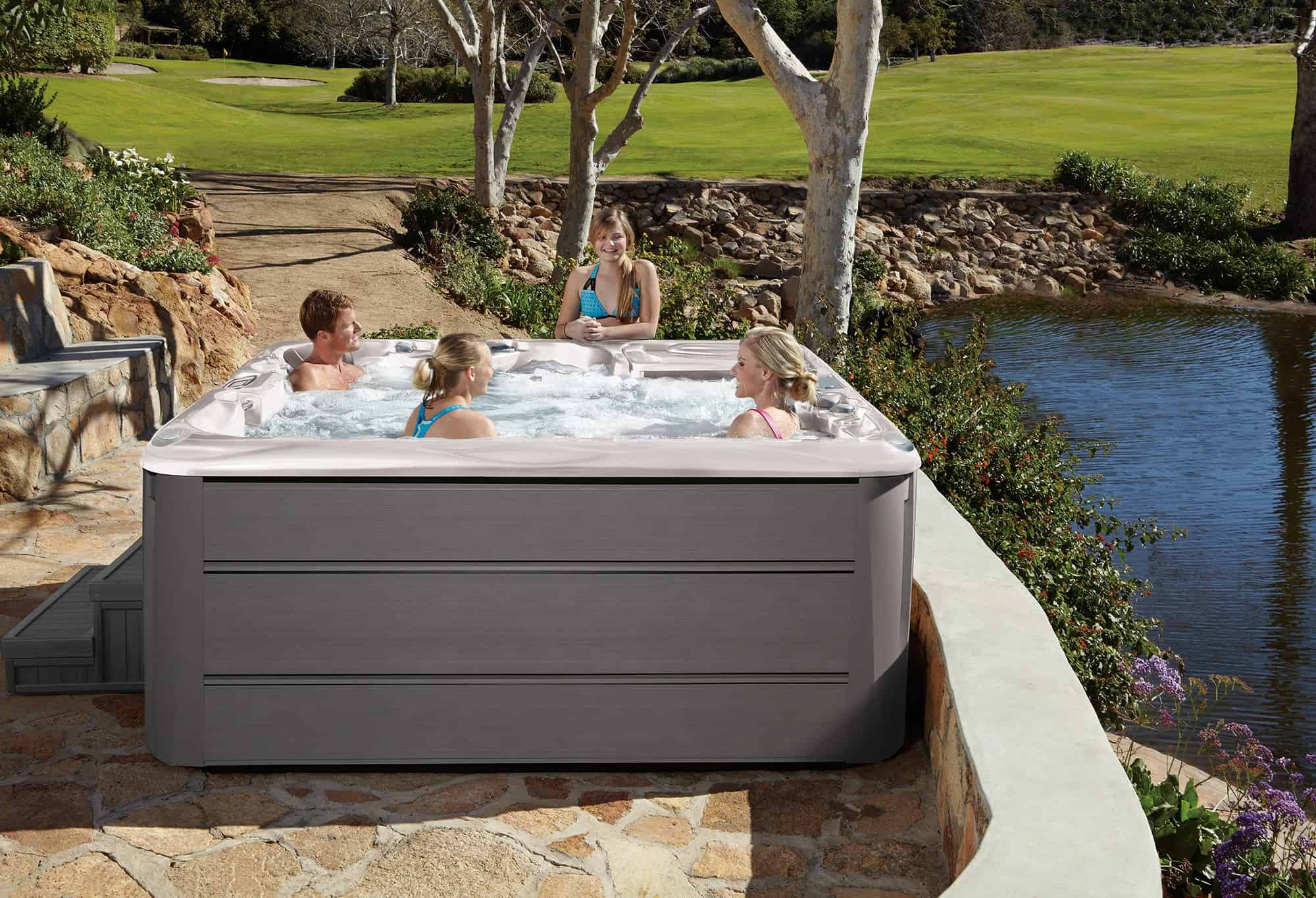 Family enjoying their Sundance Spas 880 Series Cameo by the water