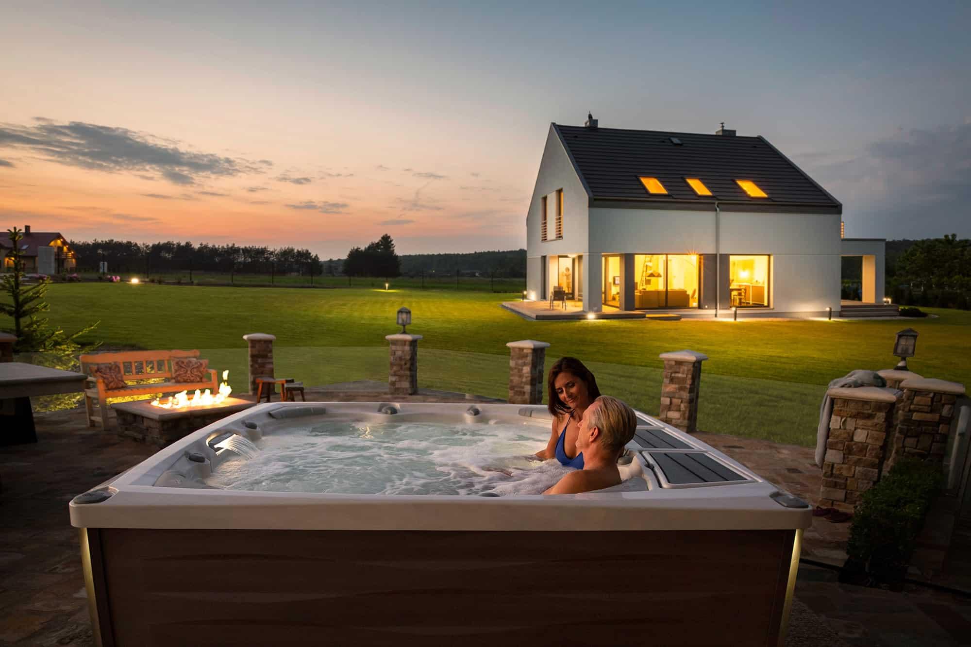 Couple enjoying their Sundance Spas hot tub at sunset