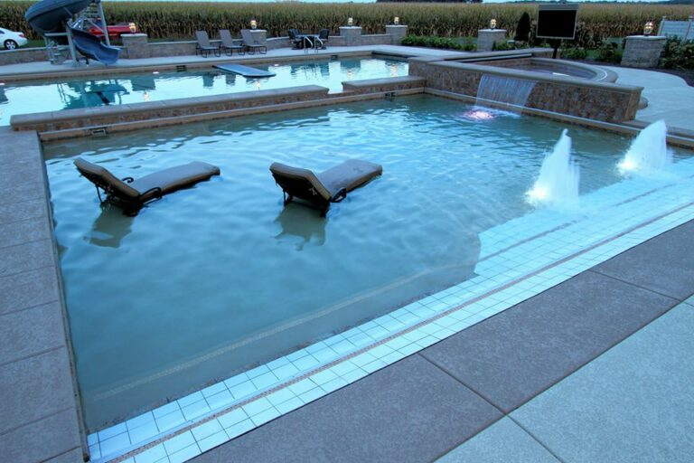 pool installation with lounge chairs waterfalls and LED lights